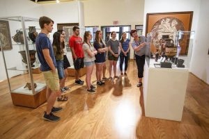 Professor Molly Pasco-Pranger in Classics provides instruction to a group of students viewing the ancient pottery collection in the UM Museum