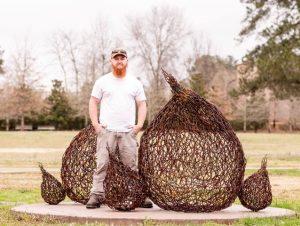 An artist standing next to a wire sculpture that looks like a bird nest