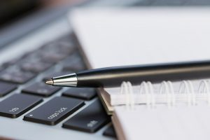 photo of pen, notebook, and computer keyboard