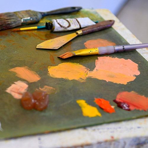 A paint palette with dabs of paint and brushes
