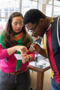 Student and Professor Cardenas look closely to book making project.