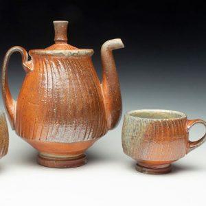 orange ceramic coffee pot and coffee cup