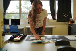 student working on her project in the graphic design computer lab