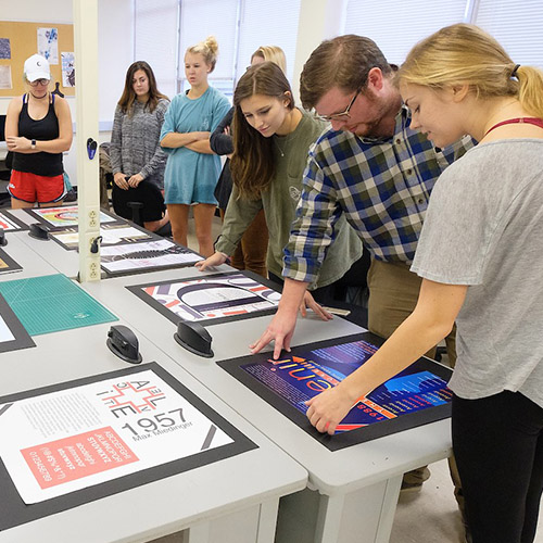 Graphic design students gathered around a table study prints of graphic art
