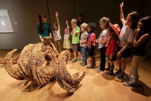A group of school children gather around a sculpture made of wood during an educational program at the UM Museum