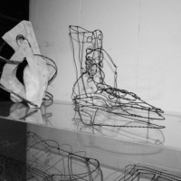 Black and white photo of wire sculptures on display.