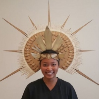 Large geometric hat with spikes on a woman's head.