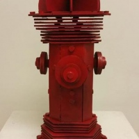 Wood cut sculpture of a red fire hydrant.