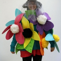 Photo of a student wearing a costume made out of giant flowers.