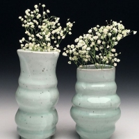 Two ceramic vases with flowers in them.