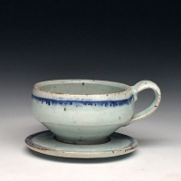 A ceramic tea cup on a saucer.