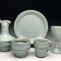 A ceramic plate, pitcher, cup, mug, and wine glass.